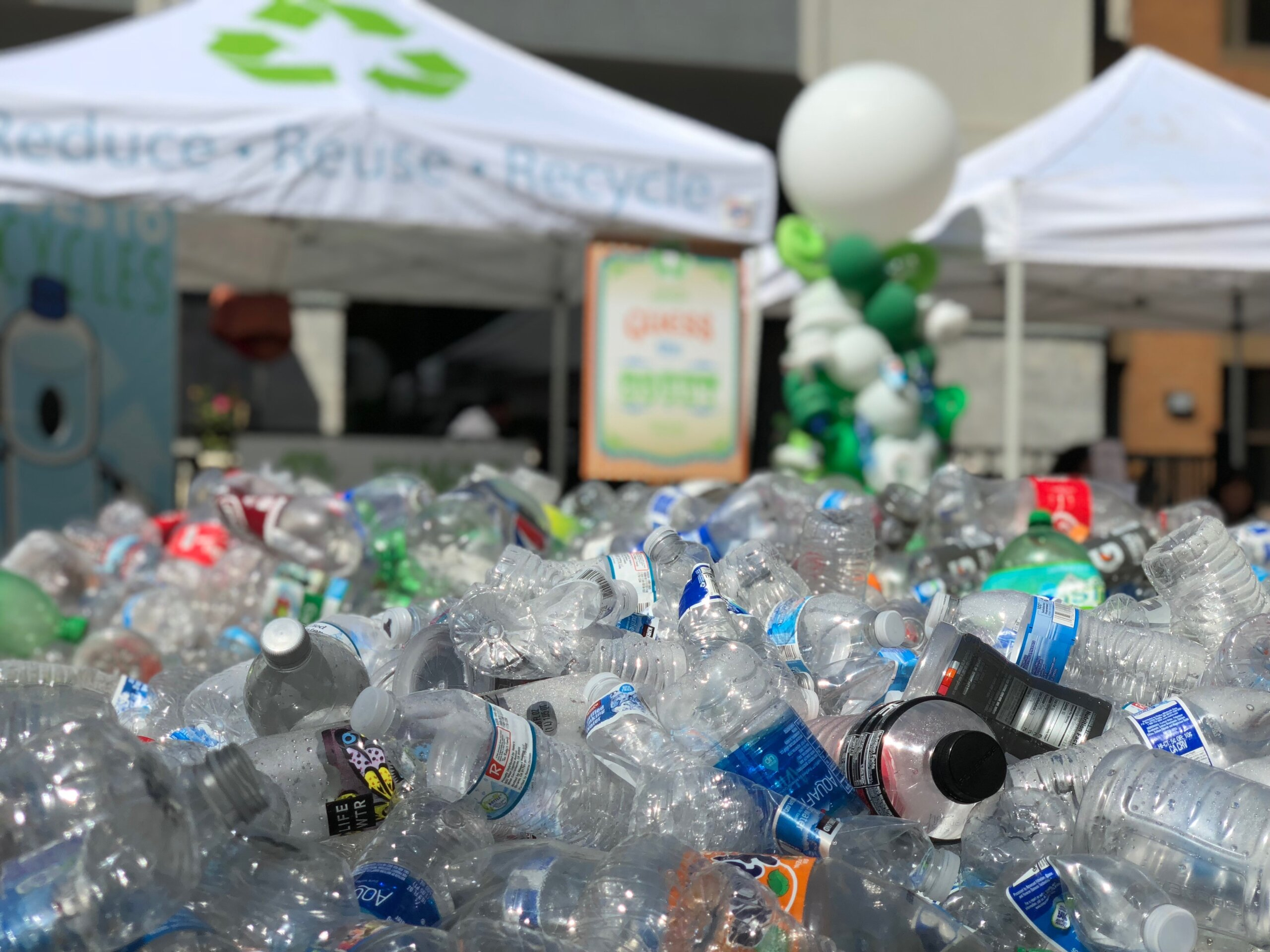 "A pile of plastic bottles in the foreground with a tent in the background that reads ""reduce, reuse, recycle"" on the canopy."