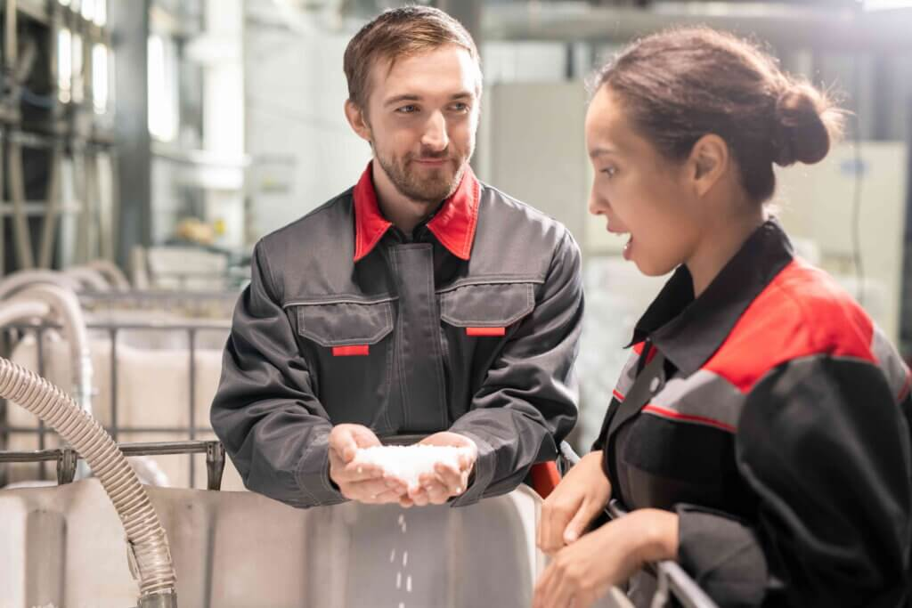 Two young quality control managers discussing characteristics of white plastic pellets while one of them holding pile over large container